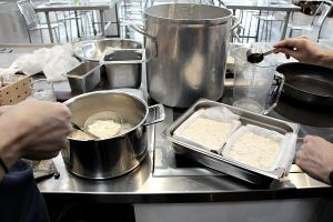 Ladling the curdled milk into prepared boxes